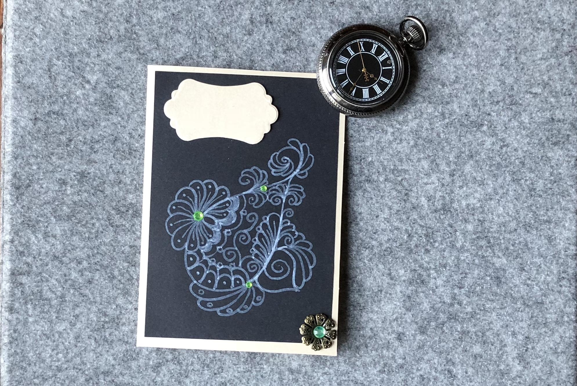 perlmuttkarte, schwarze Auflage mit weissem Stift bemalt. Verziert mit grünen Steinchen und einem Metall Vintage Sticker.