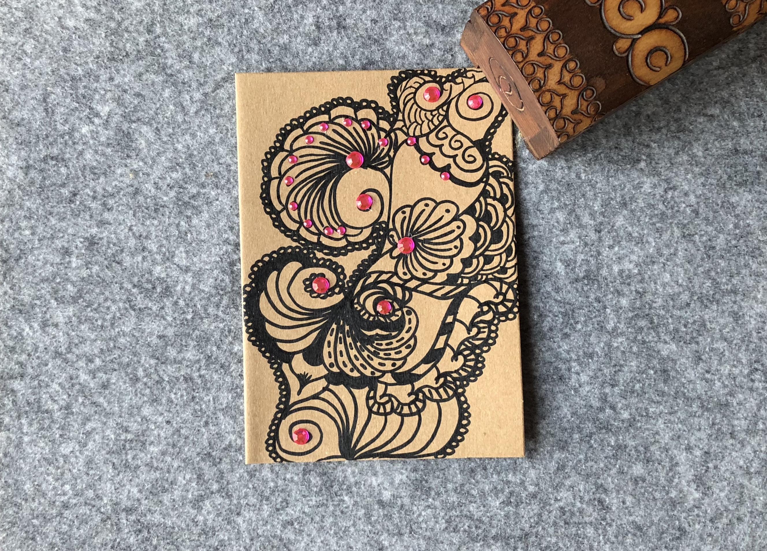 Braune Kraftkartonkarte mit einem aufgemalten Doodle verziert mit rosa Steinchen