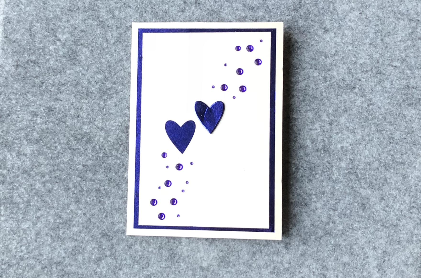 2 blaue Herzen auf Perlmutt-Hintergrund mit blauen Strasssteinen.