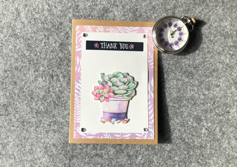 Kraftkarton-Karte. Hintegrund in rosa-lila mit weissen Blättern. Zweiter Hintergrund in weiss mit einem silbernen Sticker Thank you mit rosa Glitzerblumen. Ein Bild mit Sukkulenten in einem Blumentopf. 4 weisse Glitzersteinen an den Ecken des weissen Hintergrundes.