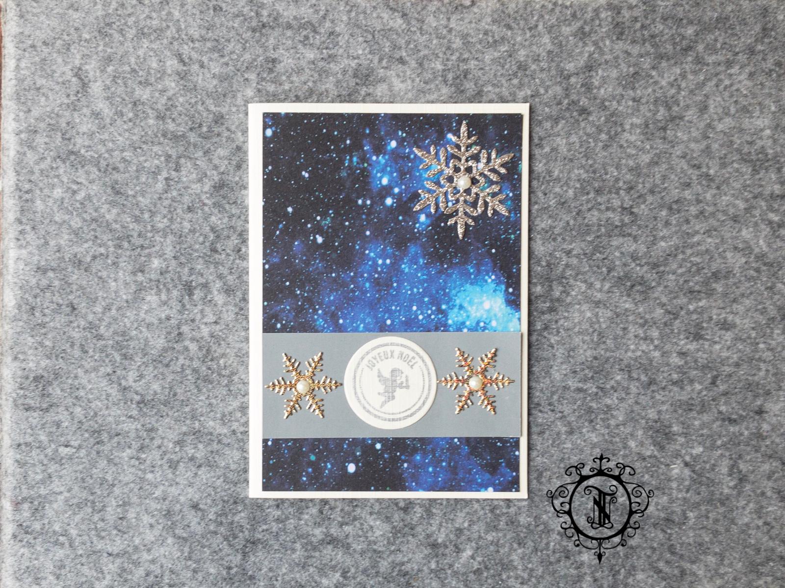 Weisse Karte. Ein Dunkelblaue Hintergrund der an das Universum errinnert. 3 ausgestanzte glitzernde Schneeflocken. Ein rundes Joyeux Noël Schild.
